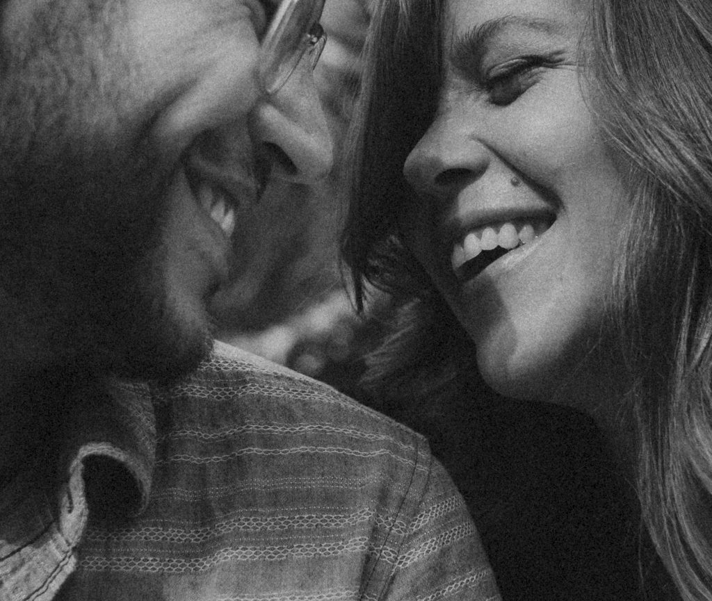 black and white photo of happy couple nose to nose laughing in love